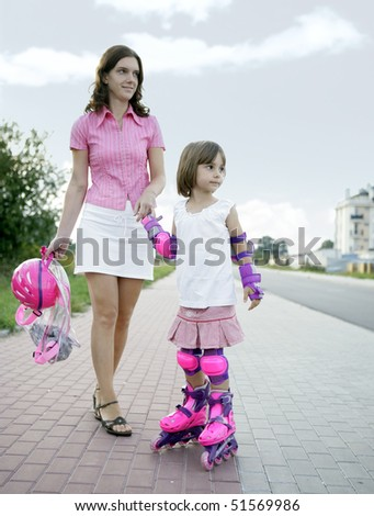 Child with mom practicing inline skating