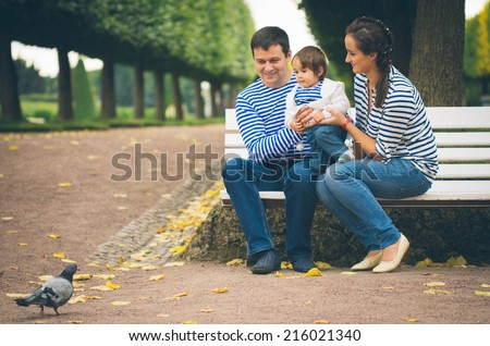 child with mother and father in the park - stock photo