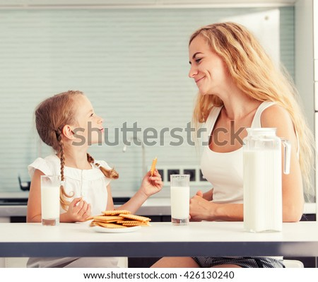 Child with mother drinking milk. Happy family eating at home - stock photo