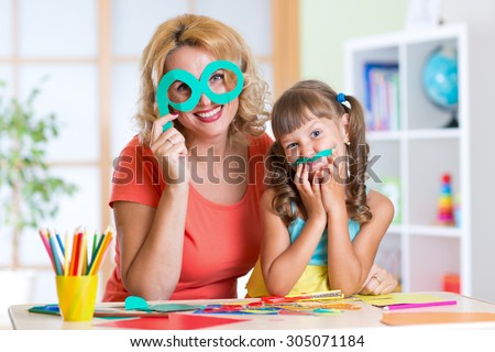 Child with mother have a fun cutting out scissors paper in preschool - stock photo
