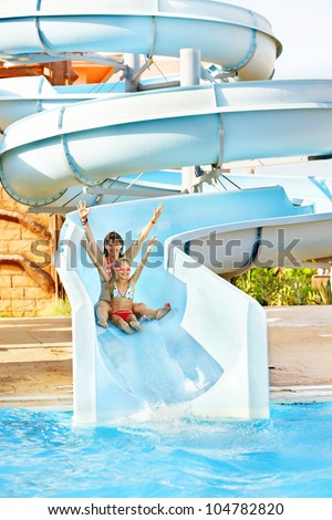 Child with mother on water slide at aquapark. - stock photo