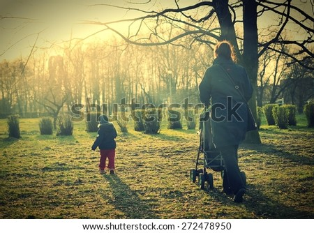 Child with mother walking in sunlight. Vintage style. - stock photo