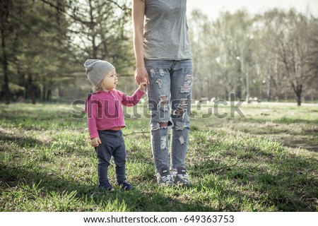 Child with mother walking together with holding hands in summer park on grass. Main subject is child. Unrecognizable mother on photo.  Concept for togetherness and care.