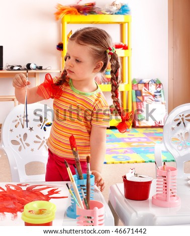 Child with paint and brush in playroom. Preschool.