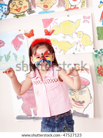 Child with paint of face in play room. Make up. - stock photo