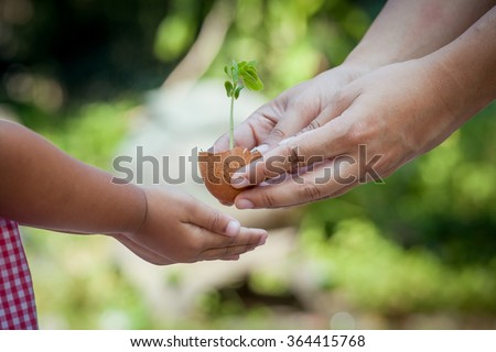 Child with parents hand holding young tree in egg shell together for prepare plant on ground,save world concept - stock photo