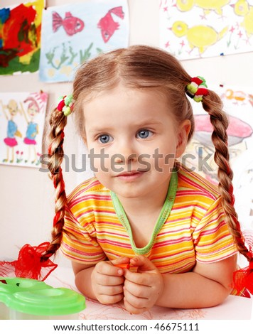 Child with piece of chalk draw  in playroom. Preschool. - stock photo