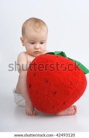 Child with plushy strawberry,on white background. - stock photo
