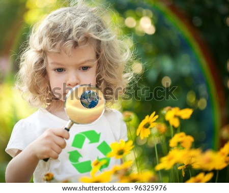 Child with recycle symbol on T-shirt looking at spring flowers against rainbow. Earth day concept.  Elements of this image furnished by NASA - stock photo