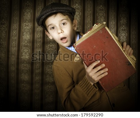 Child with red vintage book. Vintage clothes and hat - stock photo