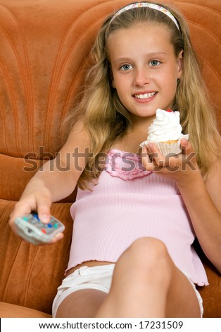 Child with remote control watching tv and eating cake - stock photo