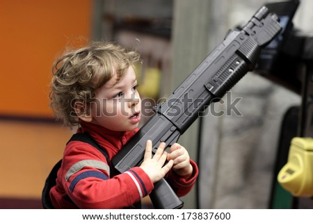 Child with rifle at an amusement park - stock photo