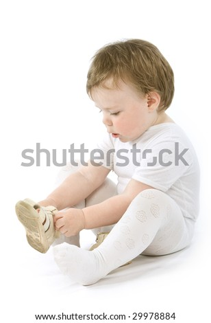 Child with shoes sitting. Isolated on white