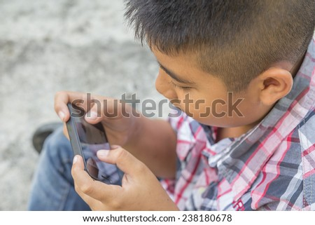 Child with smart phone. Boy play smart phone - stock photo