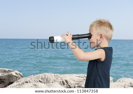 child with spyglass,outdoors at the beach - stock photo