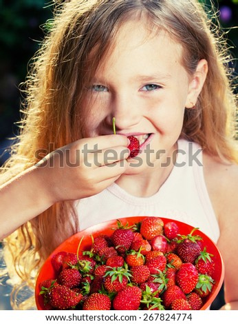 Child with strawberry. Girl with fruit, berry at garden - stock photo