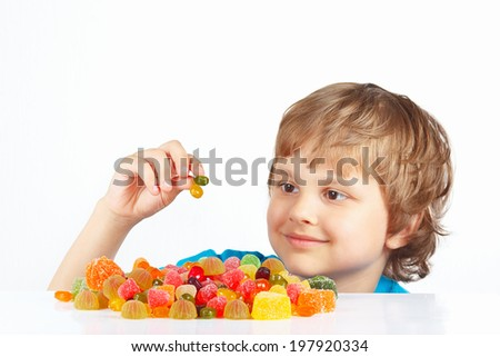 Child with sweets and candies on a white background