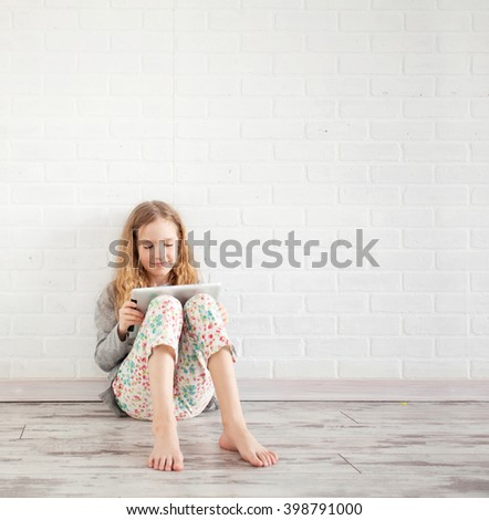 Child with tablet. Girl playing tablet at home