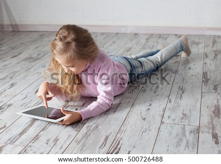 Child with tablet lying on floor. Girl playing laptop computer