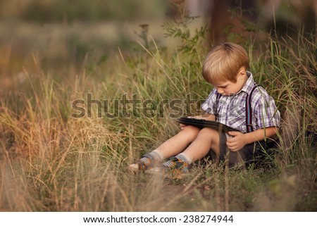 Child with tablet pc outdoors. Boy on grass with computer - stock photo