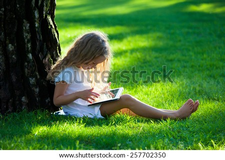 Child with tablet pc outdoors. Little girl on grass with computer - stock photo