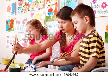 Child with teacher draw paints in play room. Preschool.. - stock photo