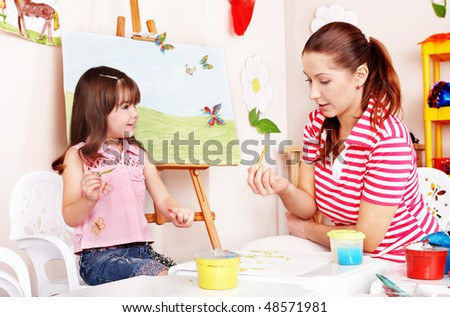 Child with teacher draw paints in play room. Preschooler. - stock photo