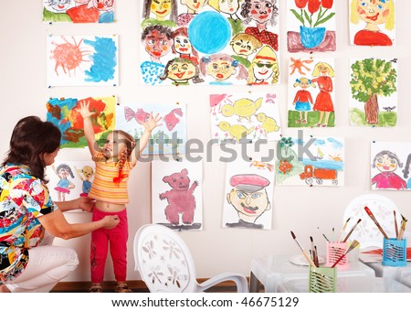 Child with teacher draw paints in playroom. Preschool. - stock photo