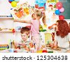 Child with teacher painting  in start school. - stock photo
