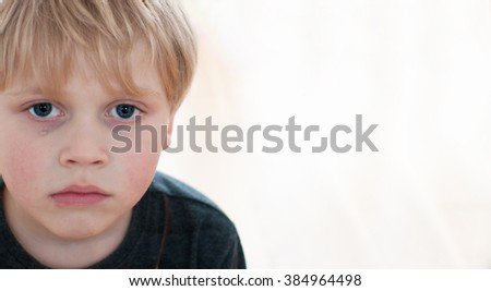 Child with tears on cheek - stock photo