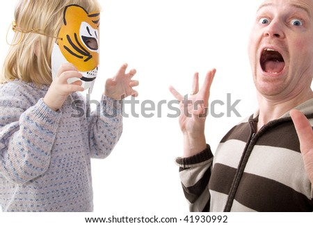 Child with tiger mask scaring adult. man in shock or surprised playing game with boy in disguise - stock photo