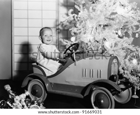 Child with toy car under Christmas tree - stock photo