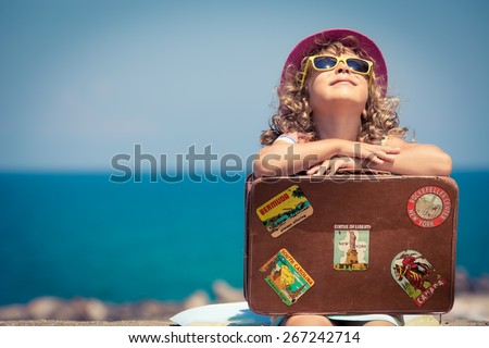Child with vintage suitcase on summer vacation. Travel and adventure concept - stock photo