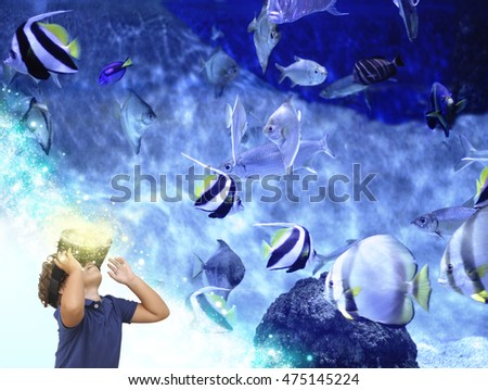 child with VR glasses playing on aquarium