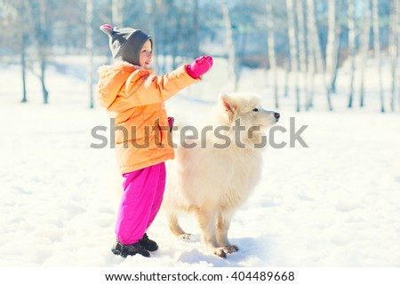 Child with white Samoyed dog on snow in winter park looking away - stock photo