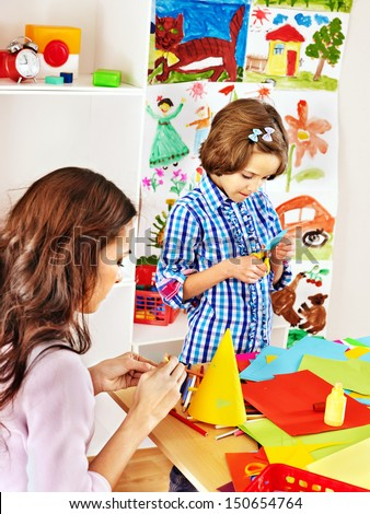 Child with woman  cutting out scissors paper in preschool. - stock photo