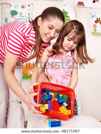 Child with wood block and construction set in play room. Preschool. - stock photo