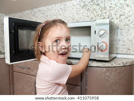 child without supervision of parents playing with microwave