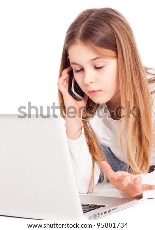 Child working on computer with phone at hands - stock photo
