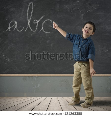 Child writing abc in a blackboard - stock photo