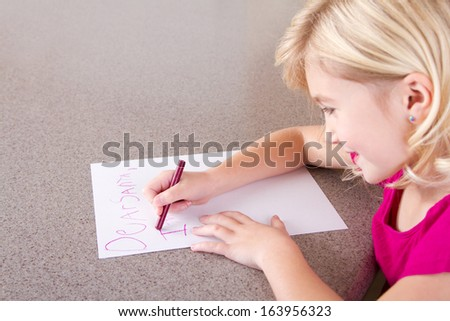 Child writing letter to Santa Claus, sitting at table