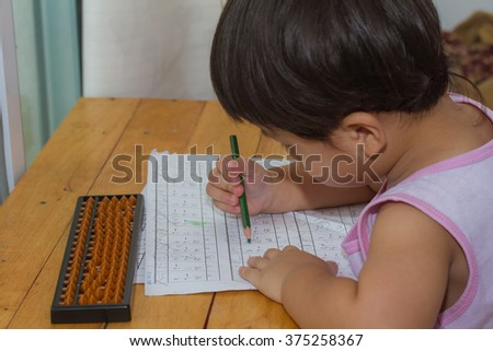 Child writing number on paper and wooden table.
