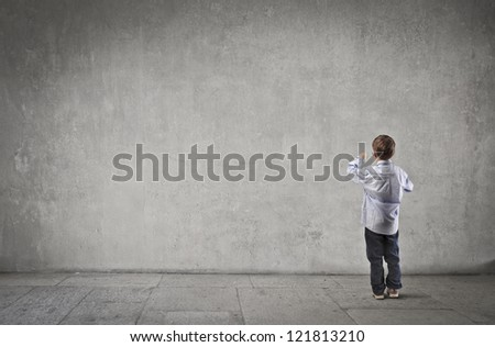 Child writing on a dark white wall - stock photo
