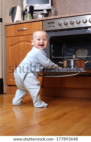 Child 1 year old in the kitchen cooking breakfast - stock photo