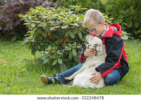 Child young boy lovingly embraces his pet dog in the garden - stock photo
