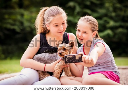 Childdren taking photo of herself and her dog - outdoor in nature - stock photo