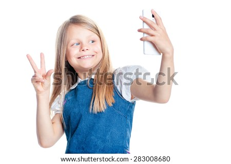 Childhood and technology. Pretty little girl taking selfie by her smartphone. Isolated on white. - stock photo