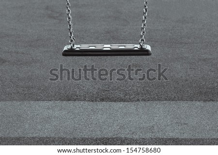 Childhood depression concept with single empty swing in black and white - stock photo