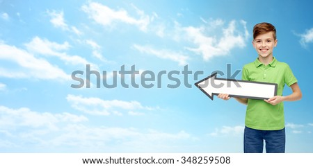 childhood, direction, advertisement and people concept - happy smiling boy in green polo t-shirt holding white blank arrow banner over blue sky and clouds background - stock photo