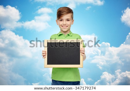 childhood, education, school, advertisement and people concept - happy smiling boy in green polo t-shirt holding black blank chalk board over blue sky and clouds background - stock photo